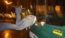 A person scavenging in a dumpster