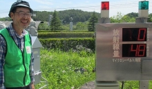 Yoichi Tao, the executive director of the volunteer group Resurrect Fukushima, stands beside an official radiation meter