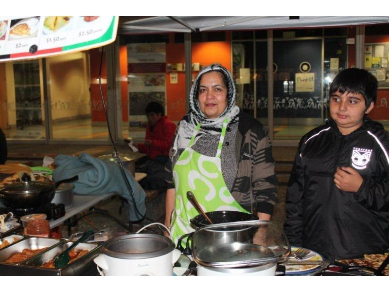 Full zarghouneh and her 10 year old nephew serve at the food stall for afghanistan