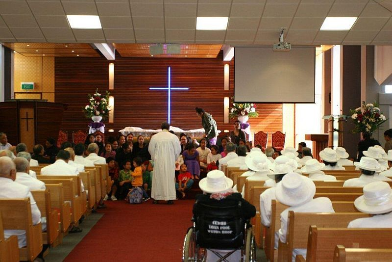 Full a sea of white  men on one side  women on the other  the pacific island presbyterian church  porirua