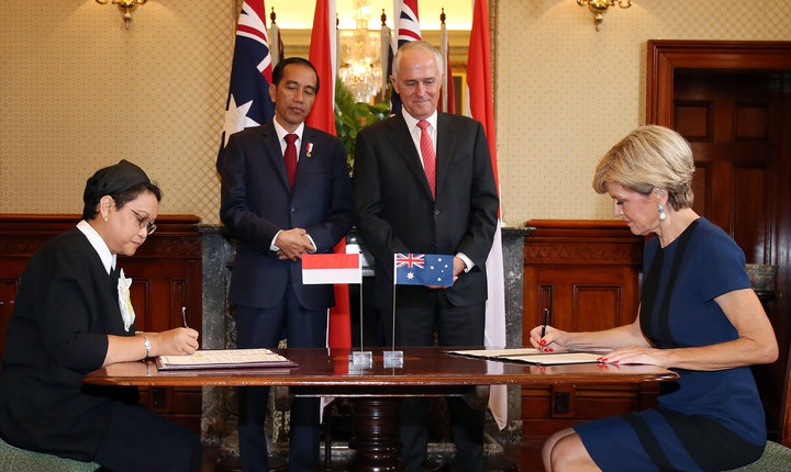Australian Minister for Foreign Affairs Julie Bishop (R) her Indonesian counterpart Retno Marsudi (L) sign official papers during a signing ceremony between the two countries as Indonesian President Joko Widodo (2nd L) and Australian Prime Minister Malcolm Turnbull look on.