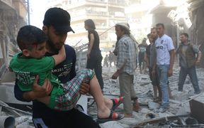 A man carries an injured child as the civil defense workers and civilians evacuate the wounded people and dead bodies pulled from the debris after Russian forces staged air-strike over residential areas in Bustan al Qasr Neighborhood of Aleppo, Syria on April 22, 2016.