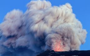 A volcano erupting, with an ash cloud exploding into the air.