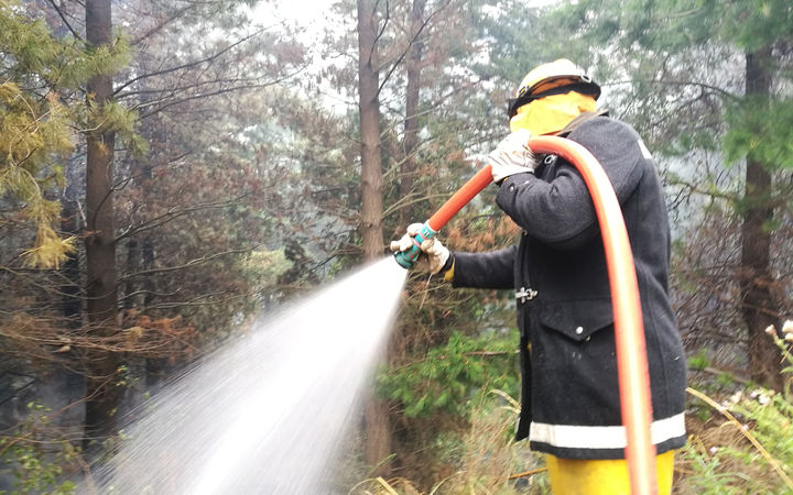 A firefighter dampens a hotspot in the Port Hills.