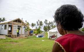 Makarita from Nukubalavu Village watches as her house is rebuilt after Cyclone Winston