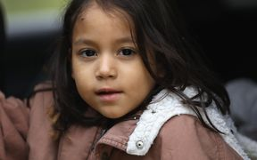 A Honduran immigrant child awaits transport by US Border Patrol agents after crossing with her family into the United States from Mexico.