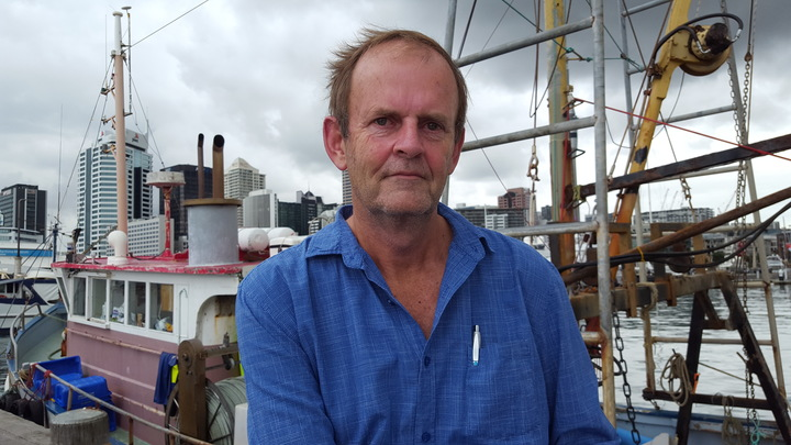 Auckland University researcher, Dr Glenn Simmons in front of fishing boats at Auckland harbour