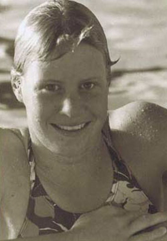 A portrait of Olympic and Commonwealth Games swimmer Rebecca Perrott leaning on the edge of a swimming pool and smiling at the camera.