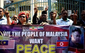 Malaysian activists show the peace sign outside the North Korean Embassy in Kuala Lumpur on Friday during a gathering urging Malaysia and North Korea to come up with a peaceful solution to the current diplomatic row.