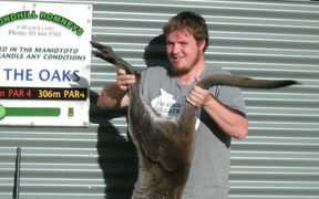 Maniototo Pest Management assistant manager Adam Mulholland with a wallaby he shot on Ranfurly Golf Course.