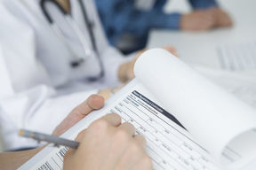 Doctor, nurse of other health worker filling out medical form