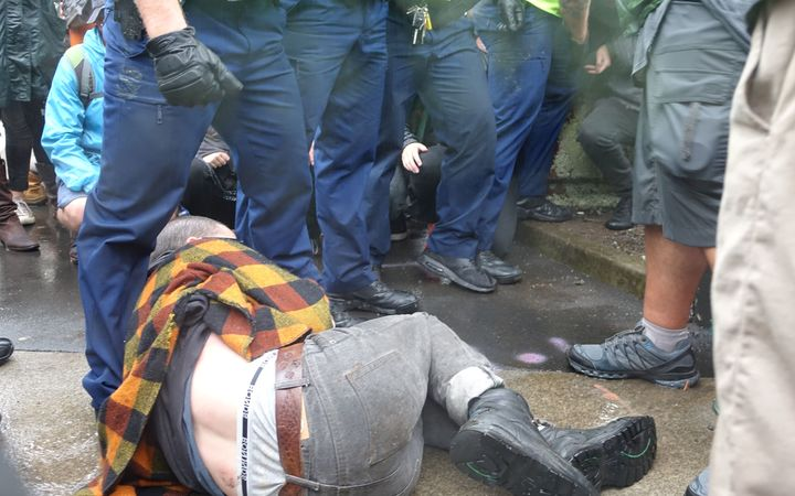 A protester on the ground, refusing to move as police try to clear a path for delegates into the conference.