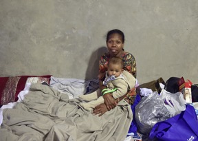 A woman and her baby take at a temporary cyclone shelter in the town of Ayr in far north Queensland.