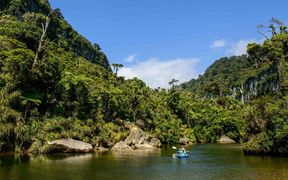 Two kayakers paddle on the Porarari River and enjoy the jungle in Paparoa National Park on February 10, 2016 in Punakaiki, New Zealand.