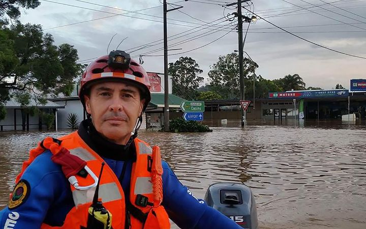 A NSW State Emergency Service worker steering his boat through the flooded streets of the northern NSW town of Lismore following Tropical Cyclone Debbie.