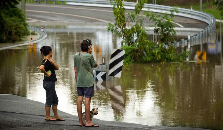 Residents watch as floodwaters caused by Cyclone Debbie recede in Beenleigh on April 2, 2017.