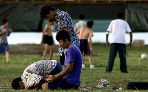 A small group of Muslim refugees pray at sunset while other refugees participate in a football match at a camp for the asylum seekers on Nauru, 20 September 2001. The first of hundreds of mainly Afghan refugees arrived on the island 19 September from the Australian troopship Manoora.