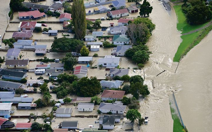 Water flows into Edgecumbe through a breach in the Rangitaiki River stopbank shortly before 9am this morning.