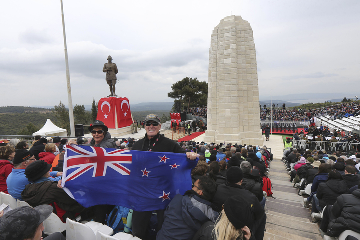 A New Zealand flag being held at a memorial service in April 2015 in front of Ataturk Memorial on Chunuk Bair near Anzac Cove in Gallipoli.