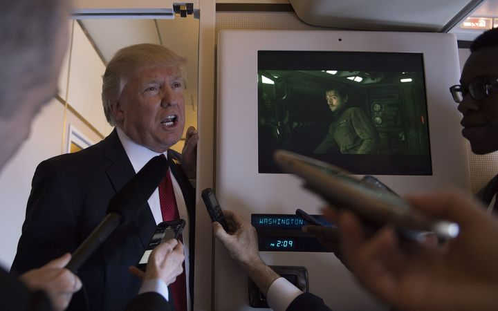 Donald Trump speaks to reporters on Airforce One.