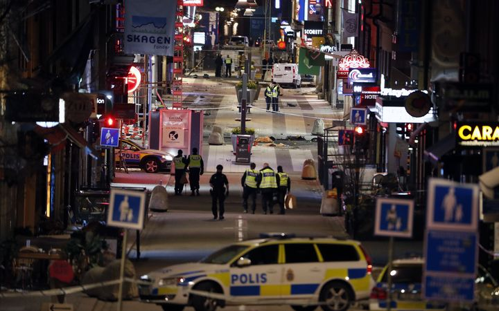Police work at the scene in to the night after a truck slammed into a crowd of people outside a busy department store in central Stockholm.