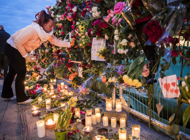 People leave tributes to those killed in an attack by the man who drove a truck through a crowd and into a storefront in Stockholm, Sweden.