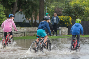 Children ride through surface flooding after the Heathcote River breached it's bank, Christchurch, New Zealand, Friday, April 14