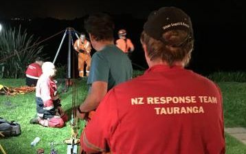 Police and volunteers worked to bring up the trapped teenager in Tauranga.