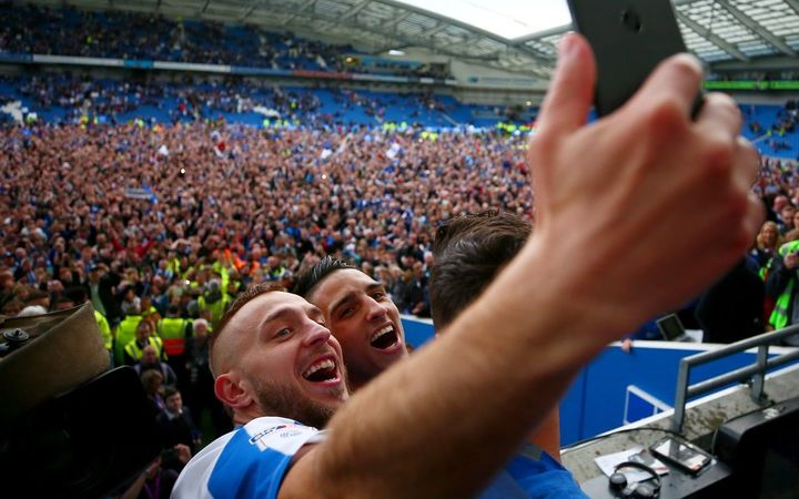 Brighton and Hove Albion players celebrate their promotion to the English Premier League.