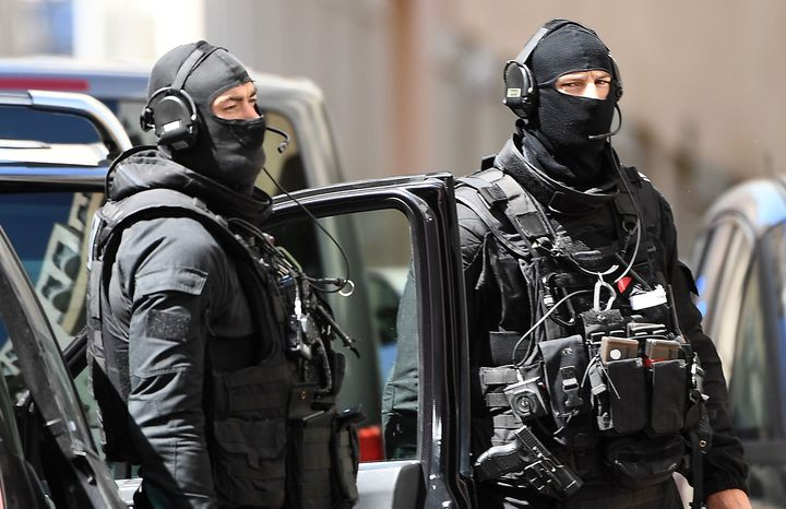 Members of the French RAID police unit leave after searching the home of one of two men arrested in Marseille on April 18, 2017