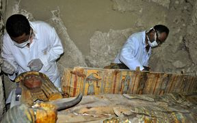 Members of an Egyptian archaeological team work on a wooden coffin discovered in a 3,500-year-old tomb in the Draa Abul Nagaa necropolis, near the southern Egyptian city of Luxor,