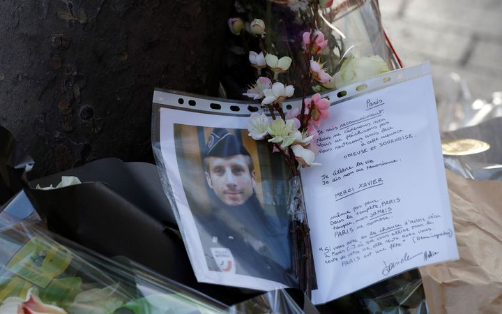A picture taken on April 21, 2017 in Paris shows a photo and a letter displayed at the site of a shooting on the Champs Elysees