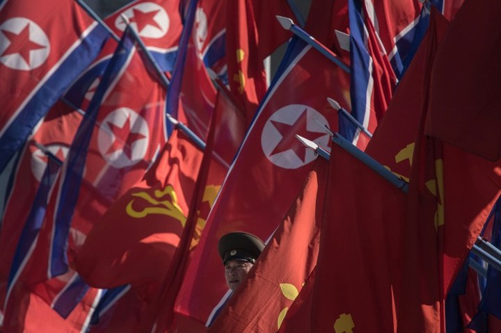 A Korean People's Army (KPA) soldier stands between flags prior to the opening ceremony for the Ryomyong Street housing development in Pyongyang on April 13, 2017.