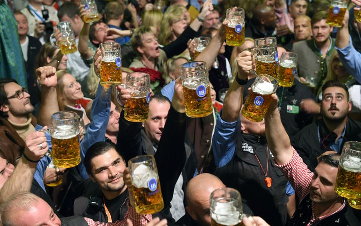Stewards raise beer glasses in the Hofbraeu tent during the finale of the 183rd Oktoberfest in Munich, Germany, 3 October 2016