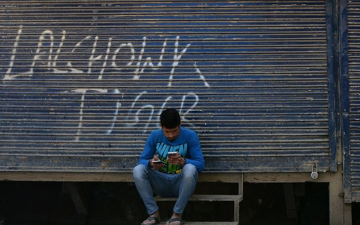 A Kashmiri man looks at his mobile phones in front of shuttered shops in Srinagar.