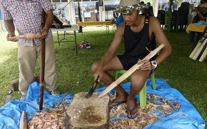 A student on Niue learns to carve in a traditional way.