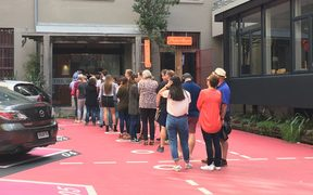 A queue forms for an open home viewing at Leeds Street apartments in Wellington.