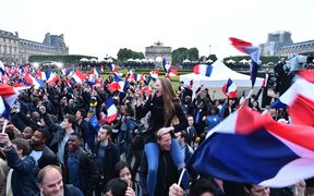 Supporters of the 'En Marche!' (Onwards!) political movement of Emmanuel Macron celebrate after the results announced at the Esplanade du Louvre in Paris.
