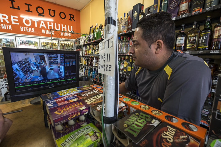 Liquor store owner Sunny Sahota looks over security footage after an incident.  Story on the daily threats storeowners have with robberies.
