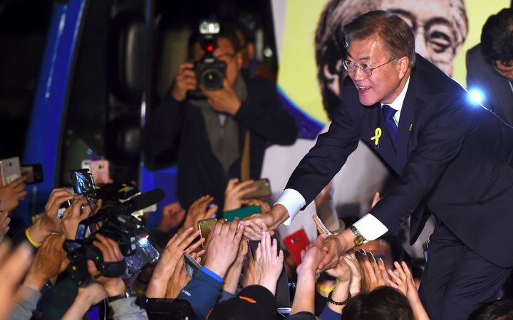 South Korean presidential candidate Moon Jae-in (R) of the Democratic Party greets his supporters as they gather to watch broadcast of the presidential election results