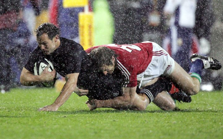 All Black fullback Leon Macdonald is tackled by Will Greenwood during the first 2005 Test.