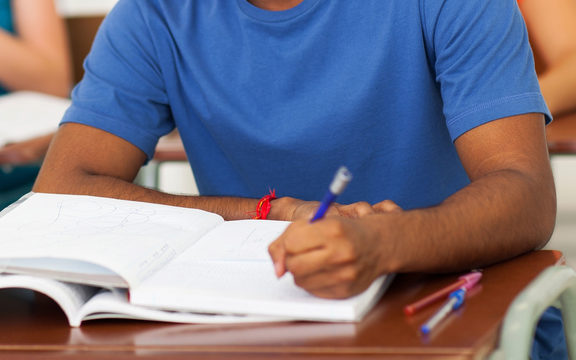 A young man in a classroom, writing, in a file photo to illustrate foreign students.