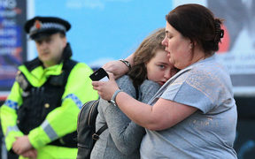 Vikki Baker and her thirteen year old daughter Charlotte hug outside the Manchester Arena
