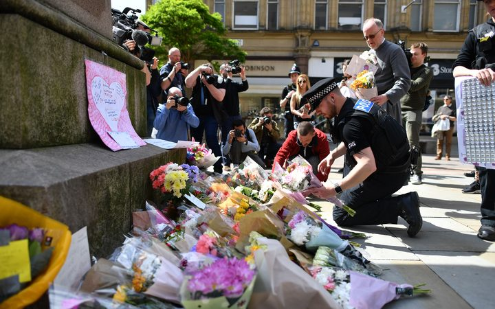 Police officers relocate floral tributes in St Ann's Square in Manchester following the attack at Manchester arena.