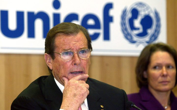 Sir Roger Moore, in his role as a UNICEF goodwill ambassador, speaks in 2003 as Christina Rau, wife of the German President at the time, looks on.