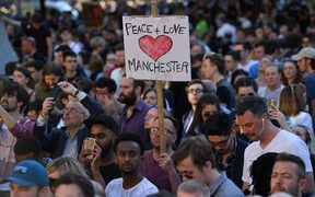 People attending a vigil at Albert Square in Manchester hold a sign 'Peace + Love Manchester.