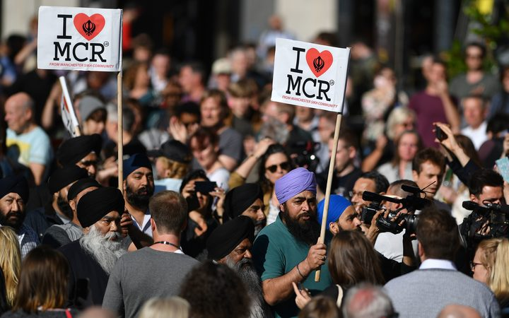 "Members of Manchester's Sikh community carry ""I love MCR"" banners as they arrive to attend the vigil following the attack at Manchester Arena."