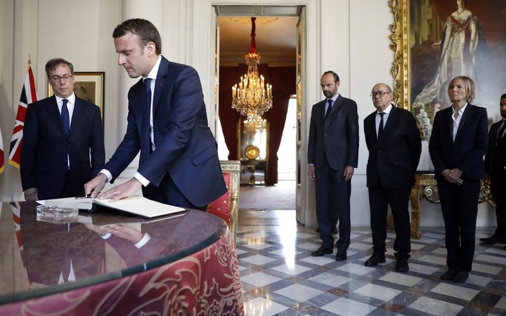 French President Emmanuel Macron signs a book of condolences at the British Embassy, flanked by English ambassador Edward Llewellyn, French Prime Minister Edouard Philippe, Foreign Affairs Minister Jean-Yves Le Drian and Minister for European Affairs Marielle de Sarnez.
