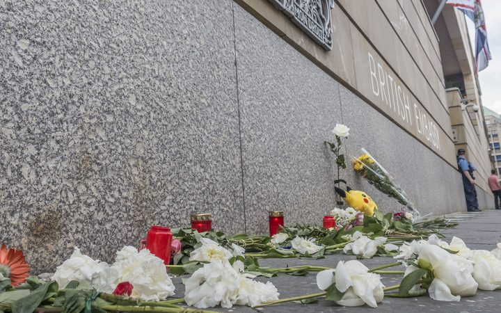 Flowers and candles are seen laid on the wall of the British Embassy in Berlin