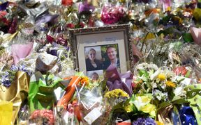 Photos showing Katrina Dawson (L) and Tori Johnson (R) sit amongst the floral tributes left outside the Lindt cafe in Sydney's Martin Place, one week after the siege.